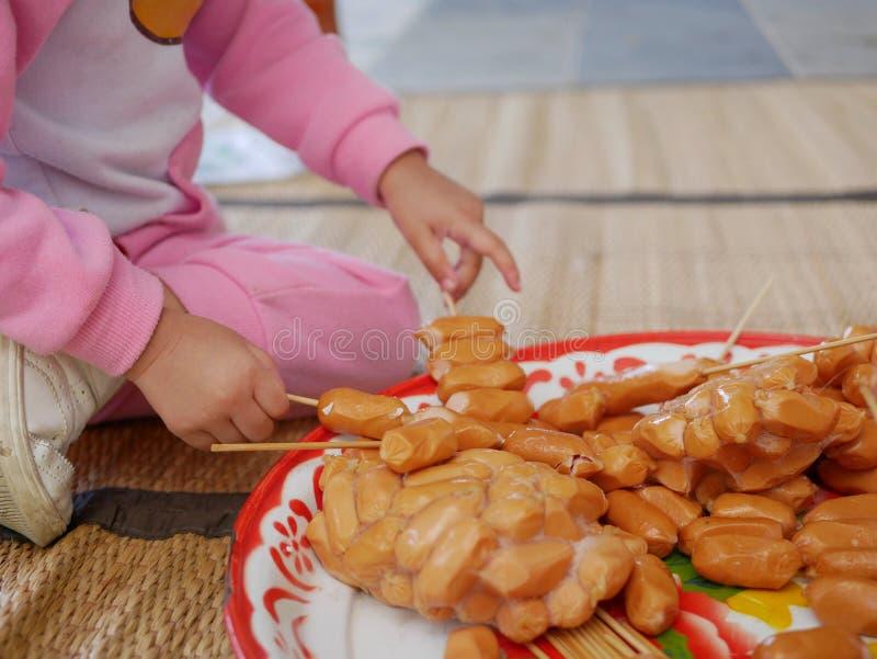 Piccolo bambino asiatico che prende i hot dog sul bastone di legno pronto ad essere cucinato immagini stock libere da diritti