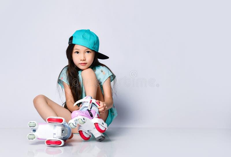 Piccolo bambino asiatico della neonata che si siede con i pattini di rullo nel sorridere felice blu-chiaro del cappuccio del capp immagini stock