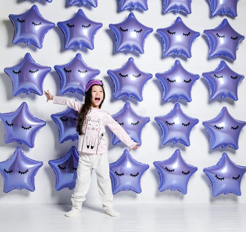 Piccolo bambino asiatico della ragazza negli sbadigli e negli allungamenti dei pigiami di mattina su fondo di grandi stelle dei p fotografia stock libera da diritti