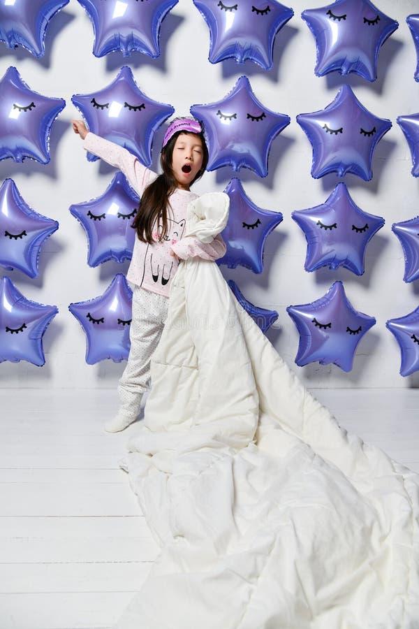 Piccolo bambino asiatico della ragazza in pigiami tiene la suoi grandi coperta e sbadigli accoglienti su fondo di grandi stelle d fotografia stock