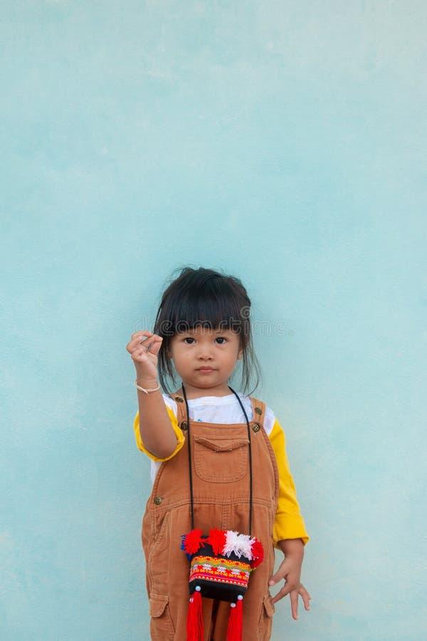 Piccolo bambino asiatico La ragazza asiatica sveglia in un vestito marrone dalla busbana francese sfoglia su mostra il cuore di a immagine stock libera da diritti