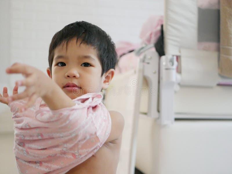 Piccolo bambino asiatico sta imparando mettere su una camicia sola fotografie stock libere da diritti