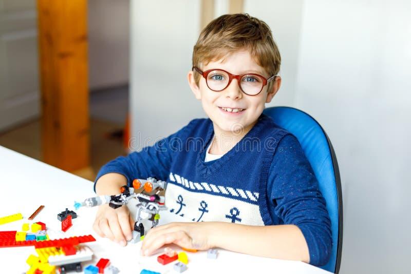 Piccolo bambino biondo con i vetri dell'occhio che giocano con i lotti dei blocchi di plastica variopinti immagini stock