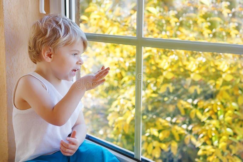 Piccolo bambino biondo sveglio che guarda dalla finestra sul autu giallo immagine stock