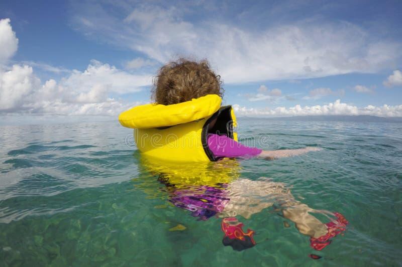 Piccolo bambino che galleggia con un giubbotto di salvataggio da solo nell'oceano immagini stock