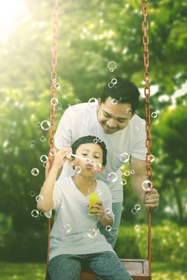 Piccolo bambino che gioca con suo padre nel parco fotografia stock libera da diritti