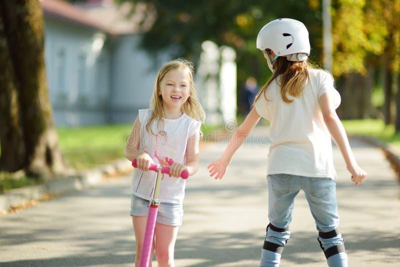 Piccolo bambino che impara guidare un motorino in un parco della città sulla sera soleggiata di estate Bambina sveglia che guida  immagini stock libere da diritti