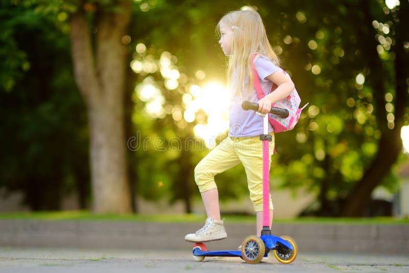 Piccolo bambino che impara guidare un motorino in un parco della città il giorno di estate soleggiato Ragazza sveglia del bambino fotografie stock libere da diritti