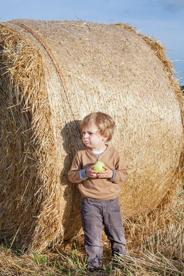 Piccolo bambino che mangia mela con una grande balla di fieno sul campo fotografia stock