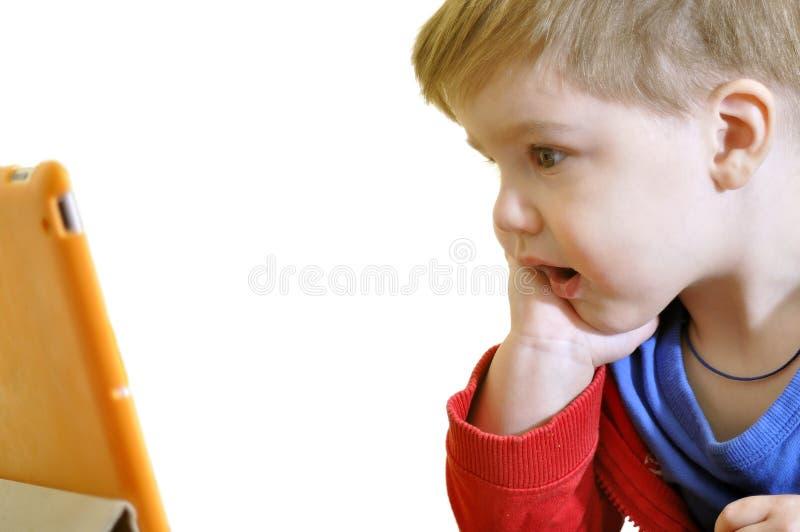 Piccolo bambino che per mezzo di un PC della compressa isolato fotografia stock