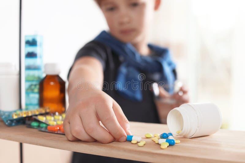 Piccolo bambino che prende le pillole dallo scaffale a casa Il pericolo di intossicazione del medicinale fotografia stock libera da diritti