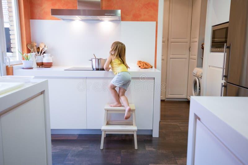 Piccolo bambino che scala su un panchetto per cucinare immagine stock