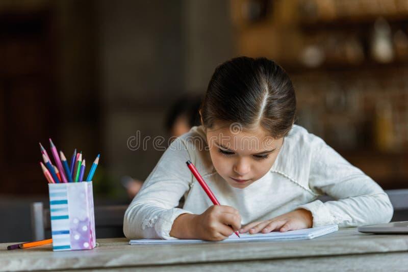 piccolo bambino che si siede alla tavola e che assorbe album per ritagli fotografie stock
