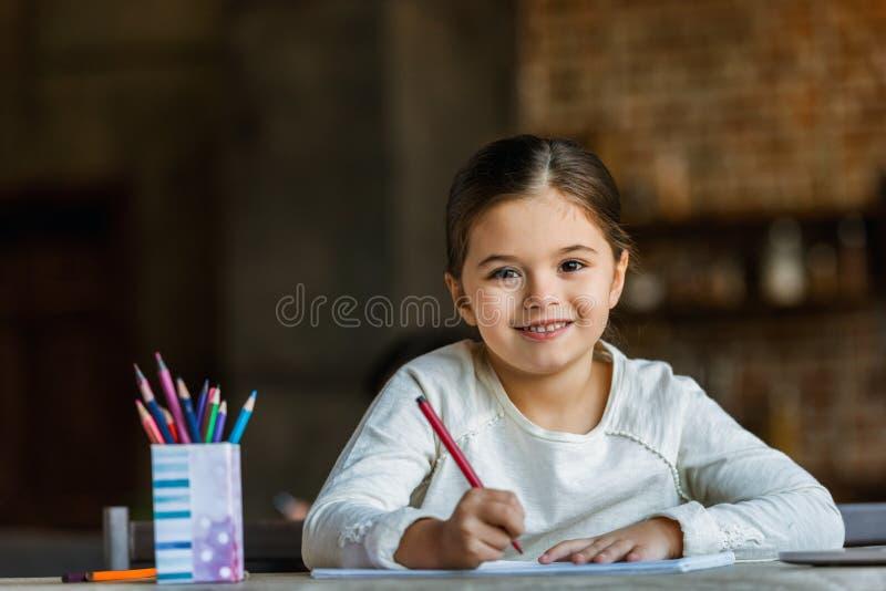 piccolo bambino che si siede alla tavola e che assorbe album per ritagli fotografia stock