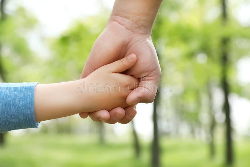 Piccolo bambino che si tiene per mano con suo padre all'aperto Tempo della famiglia fotografia stock