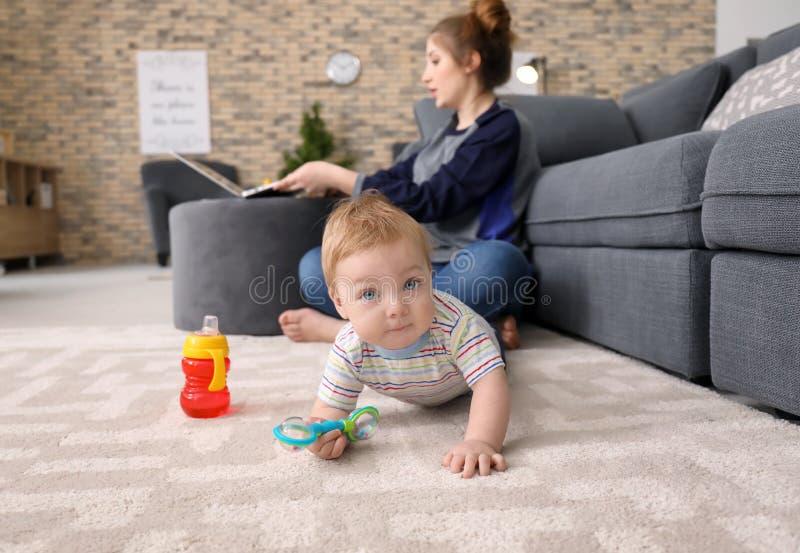 Piccolo bambino che striscia sul tappeto mentre madre che lavora a casa immagini stock