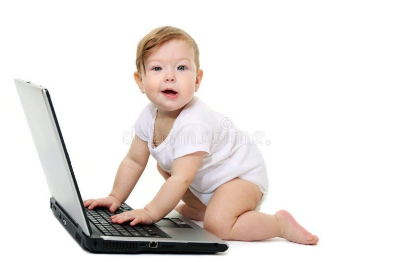 Piccolo bambino con il computer portatile immagini stock libere da diritti
