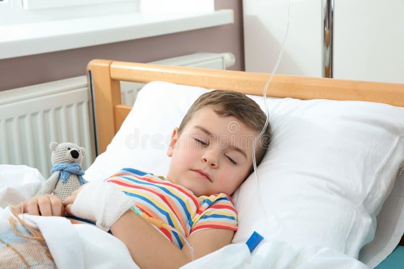 Piccolo bambino con il gocciolamento endovenoso che dorme nell'ospedale fotografie stock