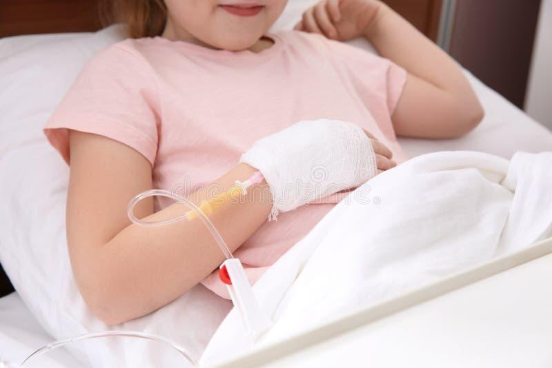 Piccolo bambino con il gocciolamento endovenoso nel letto di ospedale immagine stock