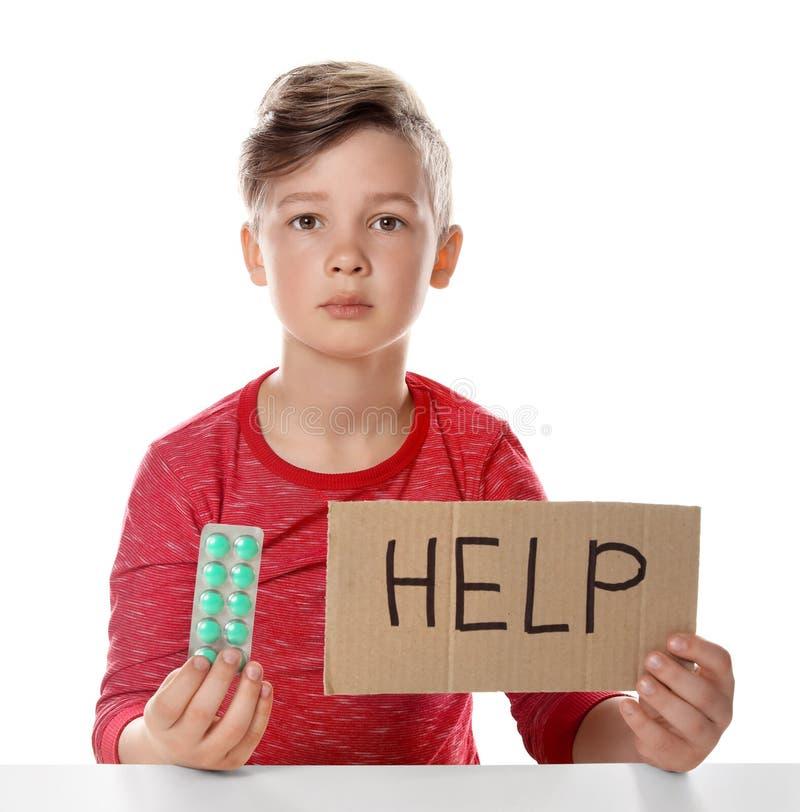Piccolo bambino con le pillole ed aiuto di parola scritto su cartone Il pericolo di intossicazione del medicinale fotografia stock libera da diritti