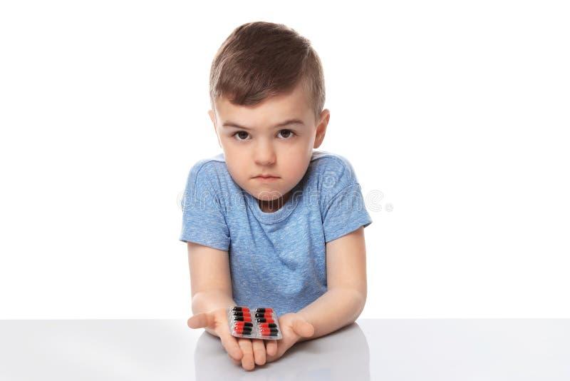 Piccolo bambino con le pillole su fondo bianco fotografie stock libere da diritti