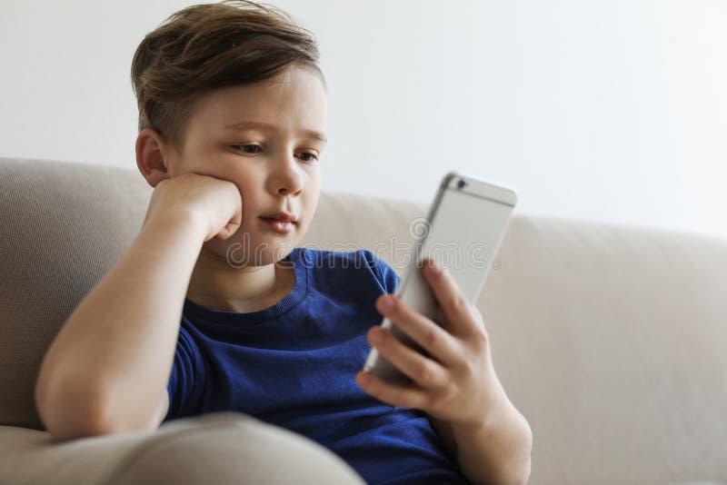 Piccolo bambino con lo smartphone sul sofà Il pericolo di Internet immagini stock libere da diritti