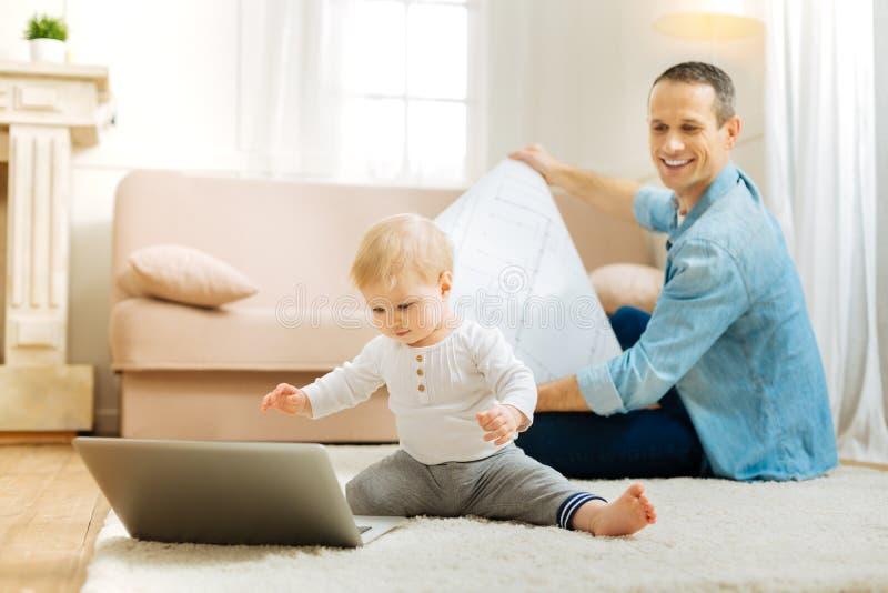 Piccolo bambino curioso che si siede davanti ad un computer portatile ed a sorridere immagine stock libera da diritti