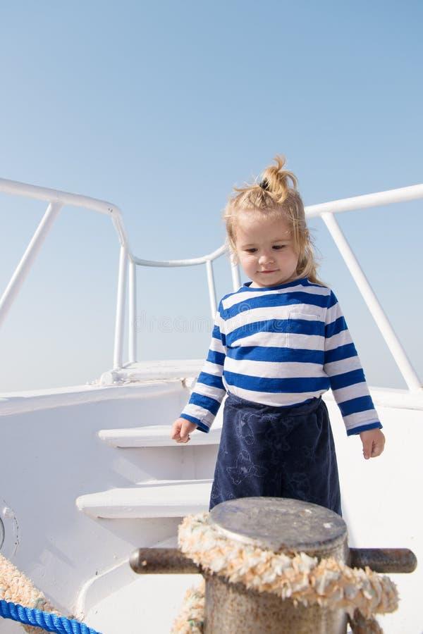 Piccolo bambino del marinaio sulla barca bambino divertente in camicia marina a strisce avventure e vacanze estive di viaggio di  fotografie stock