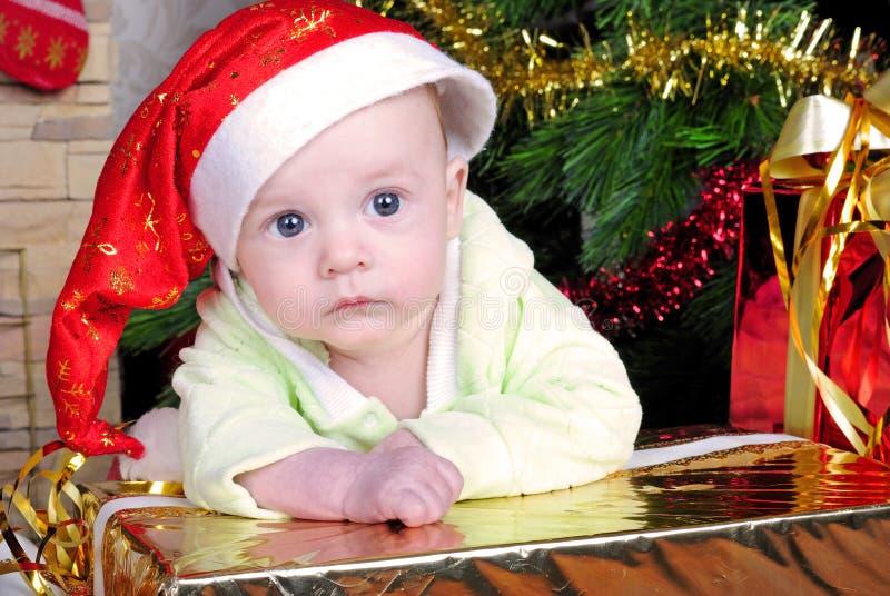 Piccolo bambino del seno vicino all'albero di abete del nuovo anno con il regalo immagine stock libera da diritti