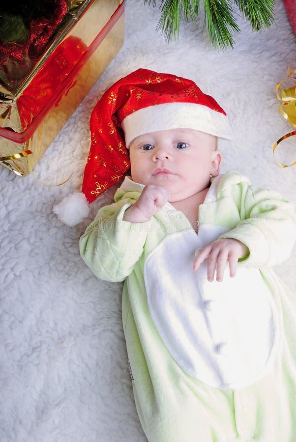 Piccolo bambino del seno vicino all'albero di abete del nuovo anno con il regalo fotografia stock