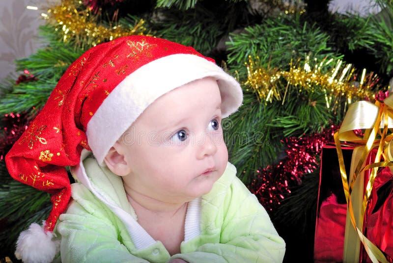 Piccolo bambino del seno vicino all'albero di abete del nuovo anno con il regalo immagini stock libere da diritti