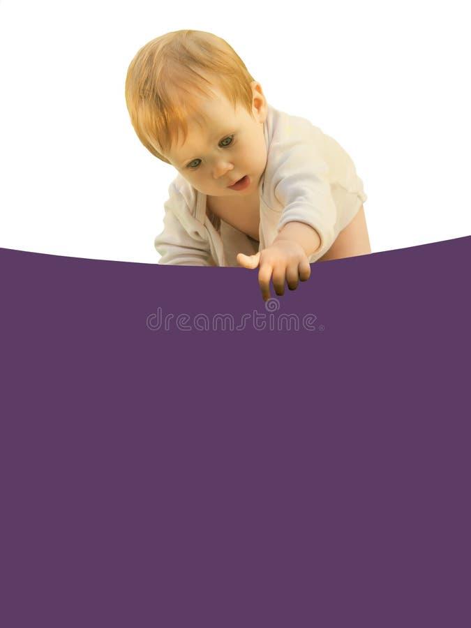 Piccolo bambino della neonata stranamente si ? chinato lo strato colorato immagini stock