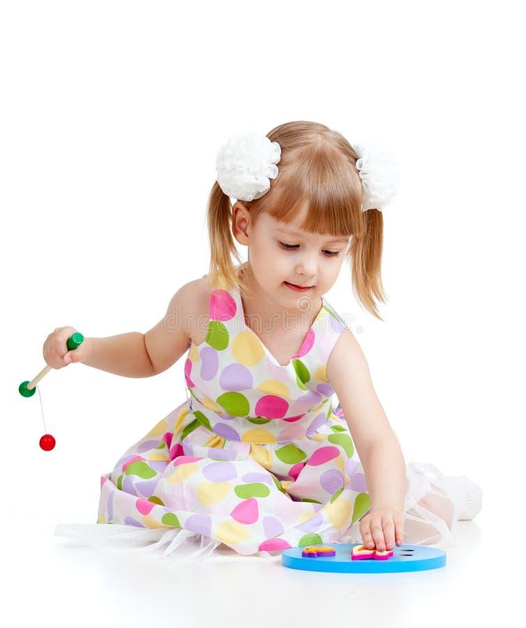 Piccolo bambino divertente che gioca con i giocattoli variopinti fotografie stock