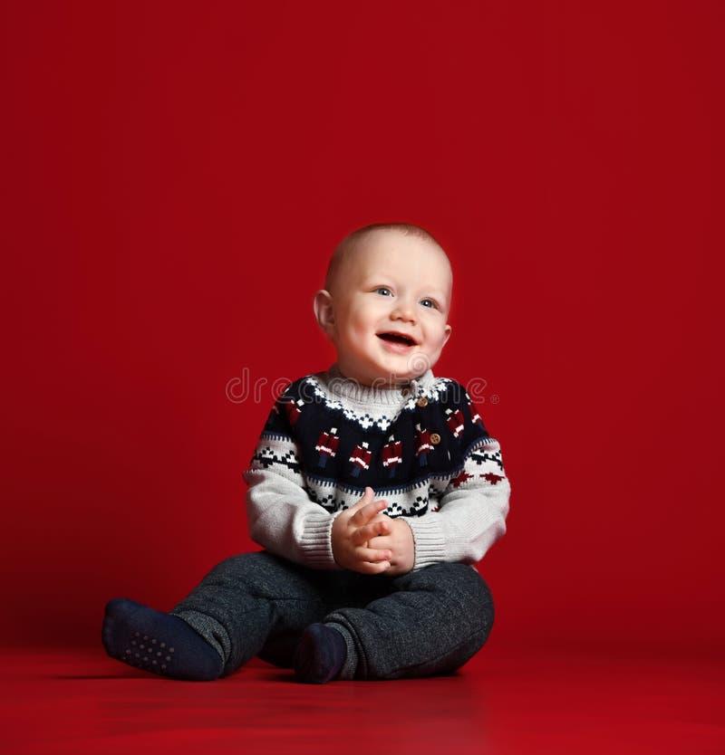 Piccolo bambino divertente che porta il maglione tricottato caldo di Natale allo studio il giorno di inverno freddo fotografie stock libere da diritti
