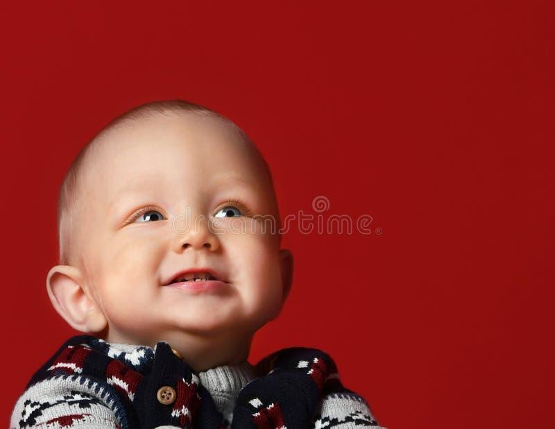Piccolo bambino divertente che porta il maglione tricottato caldo di Natale allo studio il giorno di inverno freddo fotografia stock