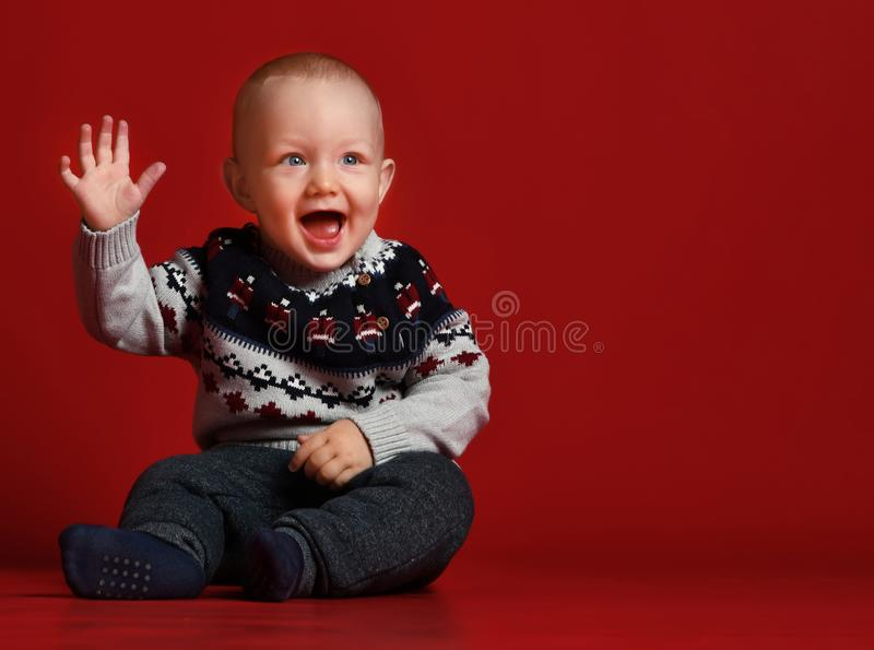 Piccolo bambino divertente che porta il maglione tricottato caldo di Natale allo studio il giorno di inverno freddo fotografie stock