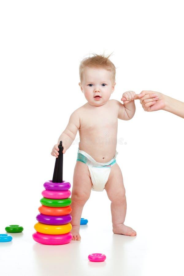 Piccolo bambino divertente che si leva in piedi con la guida della madre fotografie stock