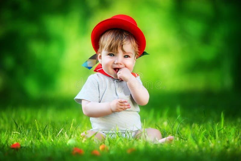 Piccolo bambino felice in cappello rosso divertendosi nel parco sul gla solare fotografia stock