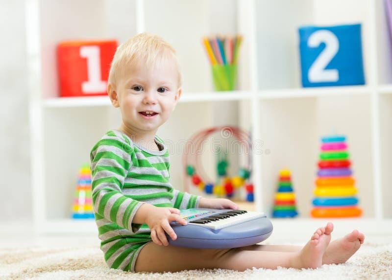 Piccolo bambino felice che gioca il giocattolo del piano fotografia stock