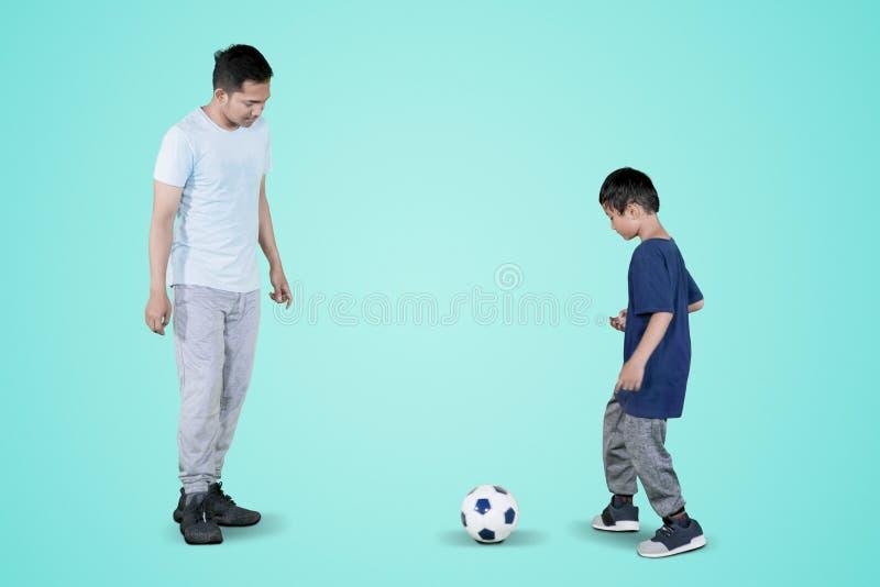 Piccolo bambino passa un calcio a suo padre sullo studio fotografia stock libera da diritti