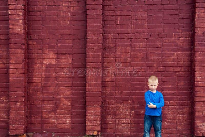 Piccolo bambino povero vicino alla grande parete fotografia stock