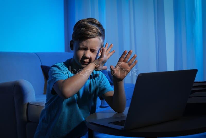 Piccolo bambino spaventato con il computer portatile Il pericolo di Internet immagine stock libera da diritti