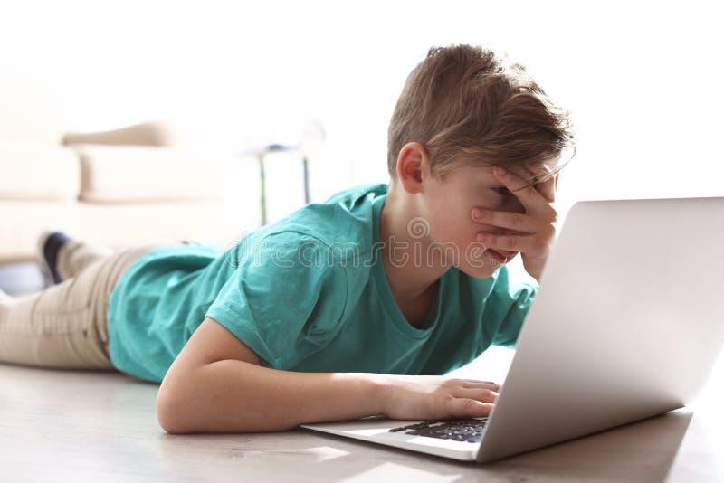 Piccolo bambino spaventato e curioso con il computer portatile sul pavimento Il pericolo di Internet immagini stock
