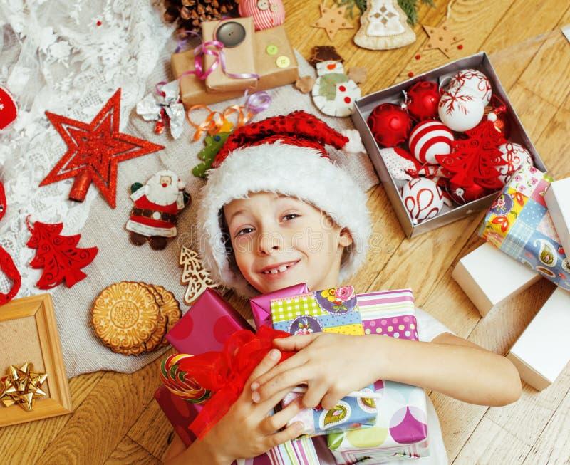Piccolo bambino sveglio in cappello rosso di Santa con i regali fatti a mano, giocattoli d'annata immagine stock libera da diritti