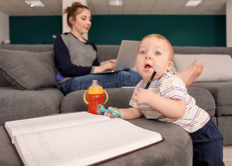 Piccolo bambino sveglio che gioca con il taccuino mentre madre che lavora a casa immagine stock