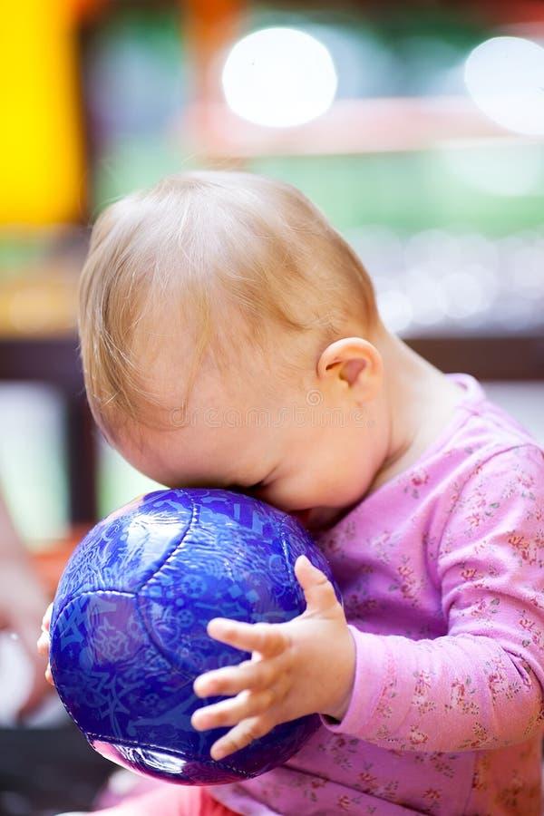 Piccolo bambino sveglio che gioca con una palla immagine stock