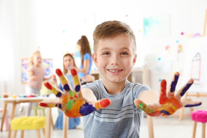 Piccolo bambino sveglio che mostra le mani dipinte alla lezione immagine stock libera da diritti
