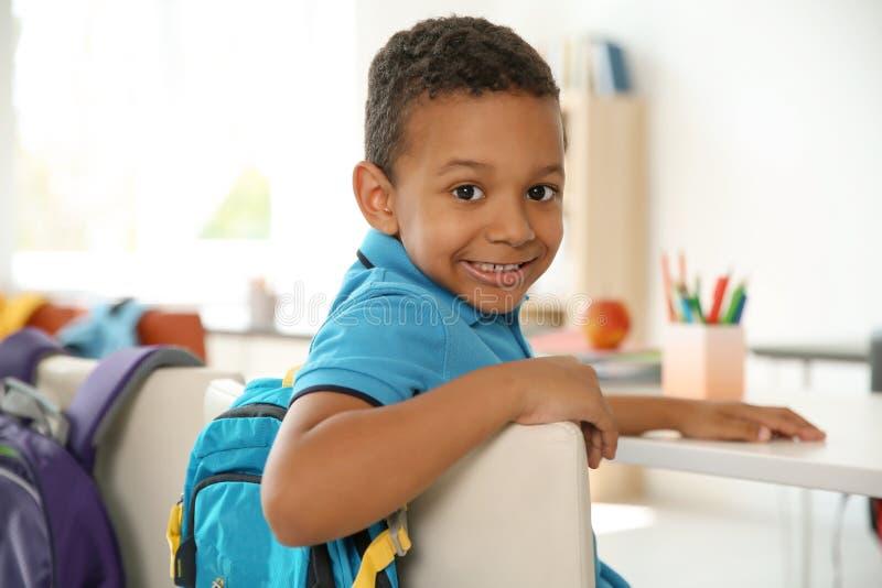 Piccolo bambino sveglio che si siede allo scrittorio in aula fotografia stock libera da diritti