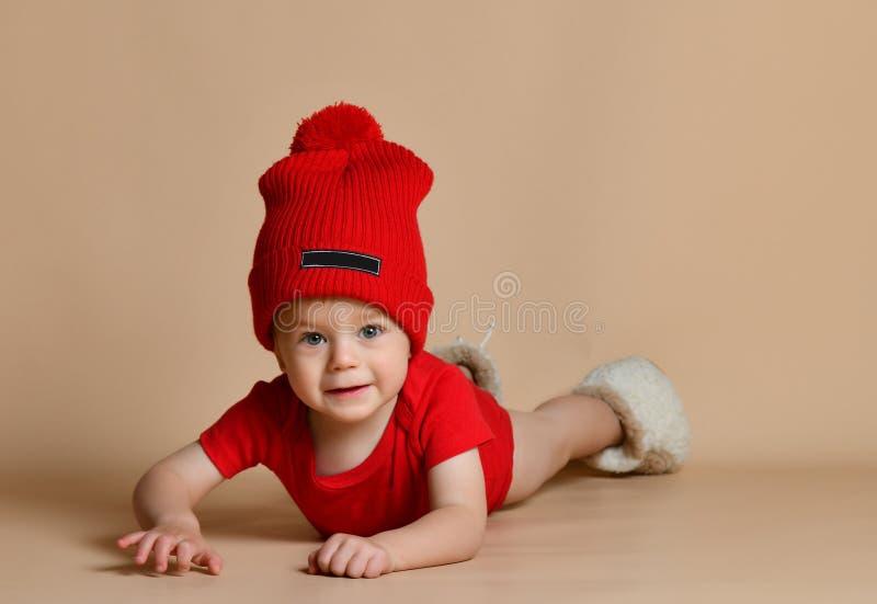 Piccolo bambino sveglio che si trova sul pavimento che guarda diritto alla macchina fotografica fotografie stock