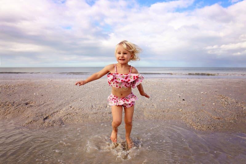 Piccolo bambino sveglio che spruzza e che gioca nell'acqua sulla spiaggia dall'oceano fotografia stock